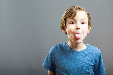 annoying child sticks out tongue