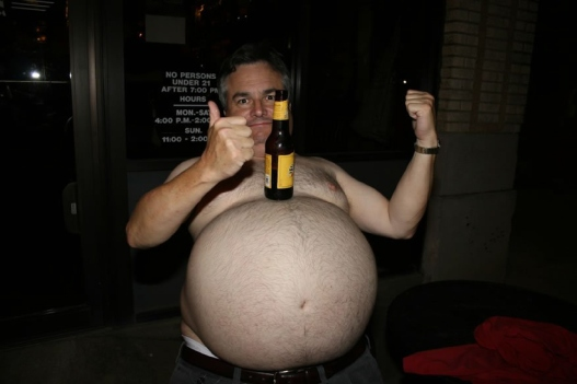 man balancing beer bottle on giant beer belly