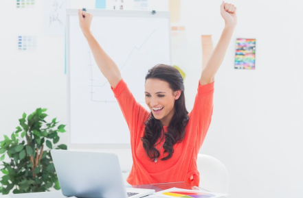 excited woman at laptop