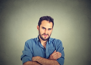 Closeup portrait of grumpy man, arms crossed, isolated on gray wall background
