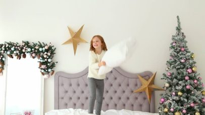 child jumping on bed Christmas morning