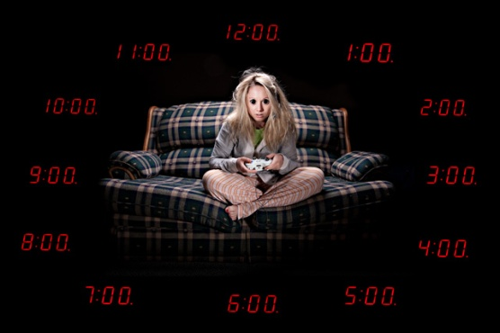 wide-eyed woman on couch playing video games surrounded by clocks showing all hours