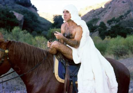 (from M.A.S.H) Max Klinger, naked, riding a horse and wearing what appears to be a long white wig.