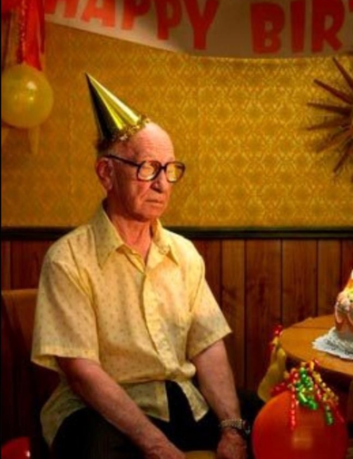 sad old man alone in birthday hat with Happy Birthday banner and cake