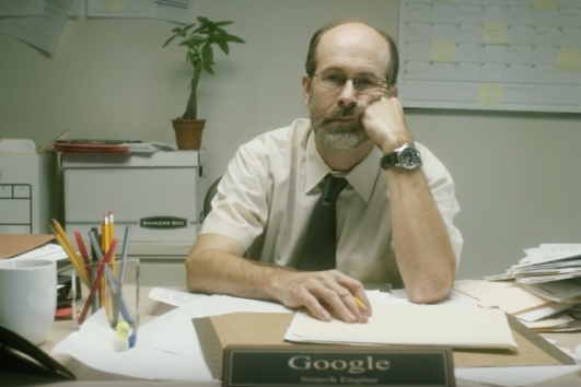 "exhausted man at cluttered desk; desk placard identifies him as Google (from ""If Google was a guy"" videos)"