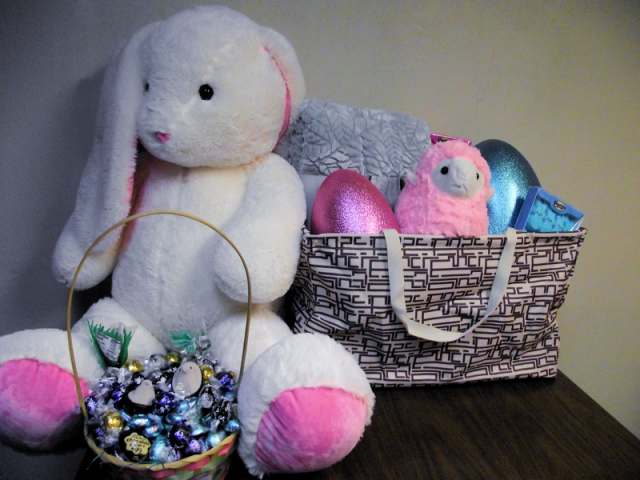 GIANT stuffed rabbit sits next to massive wireframe tote overstuffed with plush toys, glitter egg gift boxes, marshmallow peep bunnies, and more