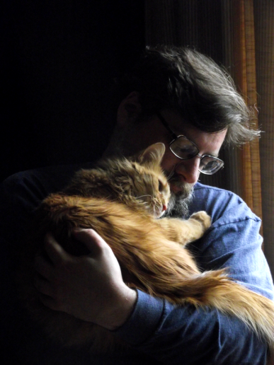 Bearded man holding and cuddling large fluffy orange cat, possibly miniature lion.