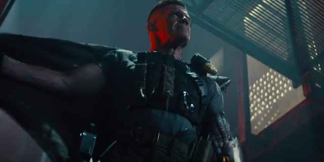 Dramatic low shot of Cable as he flings off his cape to expose a shiny Winter Soldier-style metal arm.