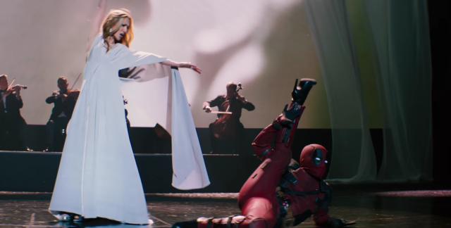 Deadpool, in full suit and stripper heels, sprawls on stage beside the incomparable Celine Dion