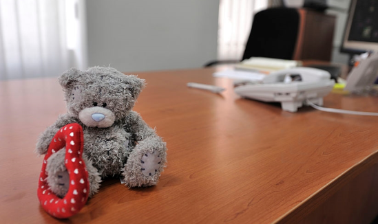 Small teddy bear holding big red heart sits alone on an executive-style desk. Judging.