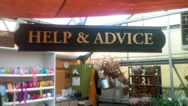 "Garden center sign reads, ""Help & Advice"" surrounded by baskets, watering cans, ribbon and plants"