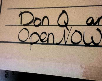 Moving box labeled Don Q and—(cut off) OPEN NOW