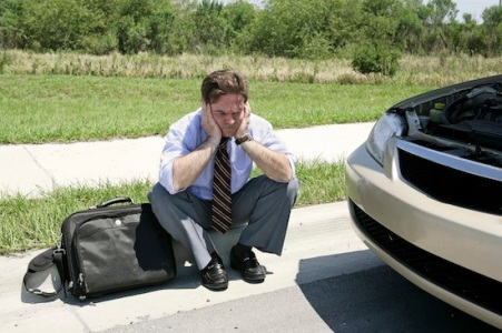 man in dress shirt and tie sits on curb between car with hood up and briefcase, waiting for roadside assistance
