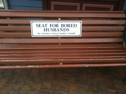 "sign on wooden bench reads, ""eat for bored husbands"" (smaller text: by coutresy Leura Country Casuals)"