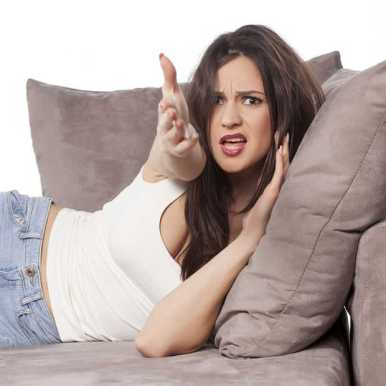 woman lounging on couch angrily gestures toward camera (the tv) yelling