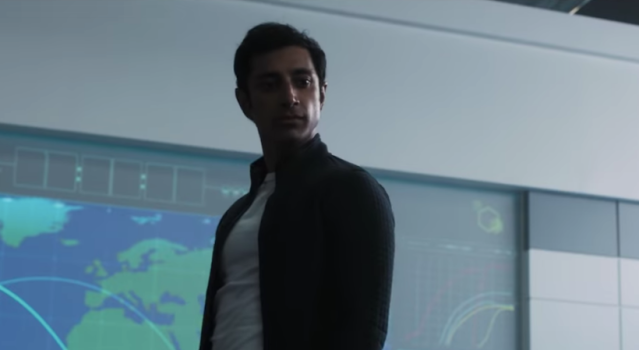 (Venom) Carlton Drake (Riz Ahmed) standing in front of a white wall with a giant screen displaying maps