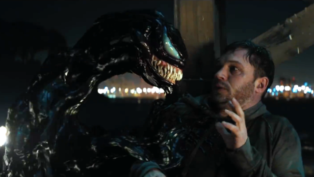 (Venom) Eddie Brock (Tom Hardy) leans away from what looks like a monster comprised entirely of oil slick, fangs, and eyes. Venom grins (having so many teeth and only so much mouth, he really has no other choice)