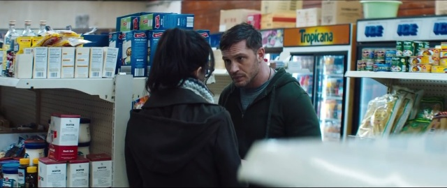 (Venom) Eddie Brock (Tom Hardy) speaks covertly with a woman in a small convenience store wedged between the ice and the marshmallow fluff