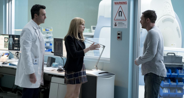 (Venom) Eddie (Tom Hardy) faces off against Anne (Michelle Williams) and a doctor in a hospital lab; an MRI machine is in the background,