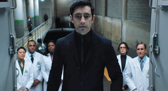 "(Venom) Carlton Drake (Riz Ahmed) faces camera, with a pack of white-coated ""scientists"" at his back"