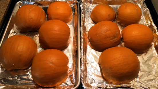 Five pie pumpkins, halved and laid out on two baking sheets.