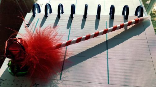 red and white ribbon-wrapped pen with red maribou feather topper and jingle bells on top; lying across open planner page.