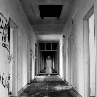 dilapidated hallway, graffiti on walls, debris on floor; blurry ghost girl in white nightgown stands halfway down, facing camera