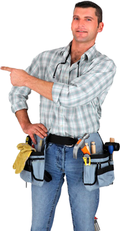 Man with toolbelt, in plaid shirt and jeans; he is smiling at camera and pointing at something behind him and to the side