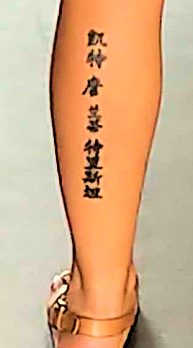 back of woman's calf, with tattoo of possibly asian language