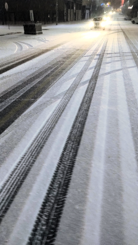 roads dusted with immesurably small quantity of snow; a car approaches with high beams on