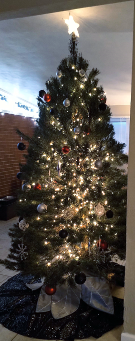 Christmas tree done up in black, silver, and red ornaments; black and silver layered tree skirt