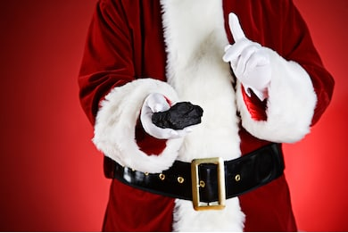 close-cropped (torso only) shot of figure in traditional red and white santa suit holding out lump of coal in one hand while shaking a finger to chastise with the other