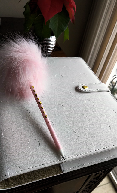 white faux leather covered planner and fluffy pink pen on desk, poinsettia in silver pot in background