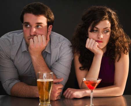 A young couple sits side-by-side, drinks at the ready, looking away from each other with bored expressions.