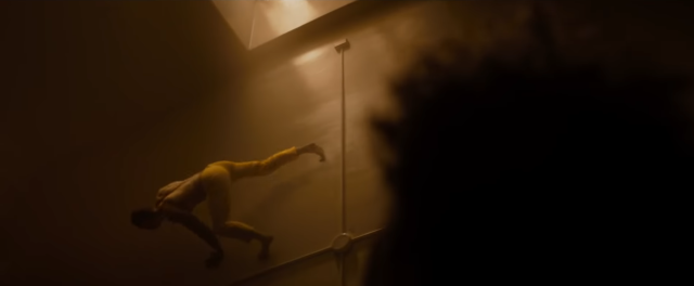 (Glass) The Beast crawling high up a smooth wall; the scene is bathed in yellow light