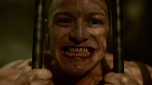 (from Split) The Beast (James McAvoy) bares bloodied teeth as he bends iron bars of a cell