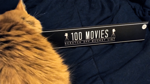 """Box (containing """"100 Movies Scratch off Bucket List"""" poster) being investigated by photo-bombing miniature lion"""