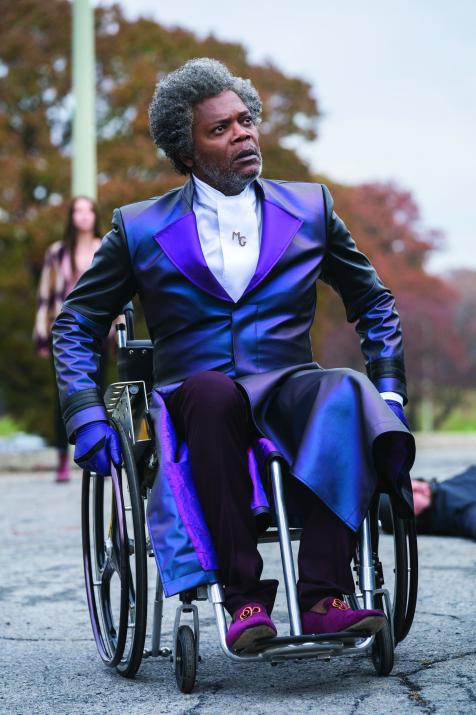 (Glass) Samuel L Jackson wheeling along outdoors in full Mr. Glass regalia; the long purple coat, purple loafers, the ascot with MG monogrammed pin, and purple leather gloves.