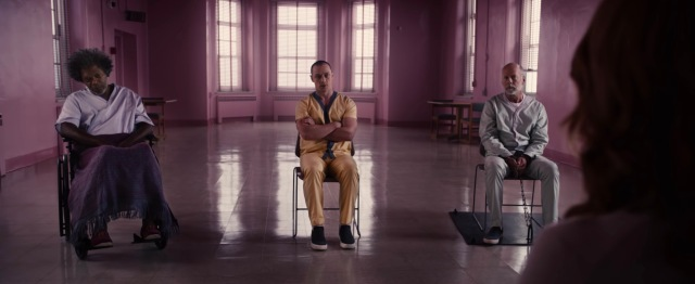 (Glass) Elijah Price sits infirm in his wheelchair, one of Kevin's personalities crosses his arms angrily, and David Dunn seems annoyed to be the only one of this trio chained to the floor; the room is bathed in an eerie pink light. Sarah Paulson's hair is visible in the foreground.