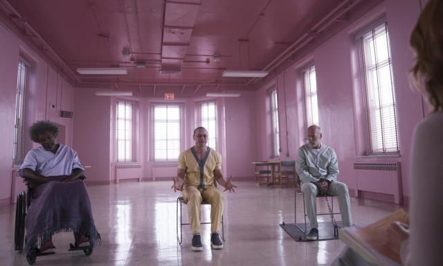 (Glass) in the pink lit therapy room, Sarah Paulson takes notes while James McAvoy becomes agitated. Bruce Willis looks on and Samuel L Jackson pretends to drool on himself