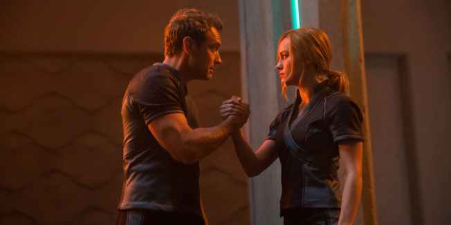(Captain Marvel) Jude Law and Brie Larson clasp hands in an earnest moment while training