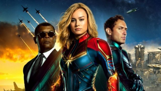 Captan Marvel poster featuring Captain Marvel, Nick Fury, and Yon-Rogg against a backdrop of futuristic cities, modern human jets, and explosions in space