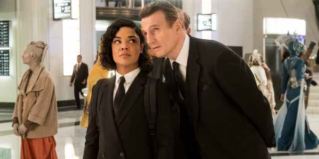 (MiB International) Liam Neeson leans over to whisper in Tessa Thompson's ear, surrounded by aliens and MiB agents