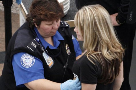 woman receiving over-the-blouse breast exam by TSA agent
