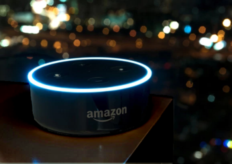 Amazon Echo Dot with illuminated ring in front of window, city night view