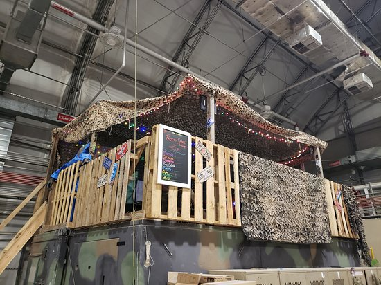 "clubhouse/lounge in Bagram hanger, made of ""tactically acquired"" pallets and bits of wood, covered with a tarp. Strung with Christmas lights."