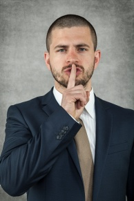 Man in suit making shh gesture (finger to lips)