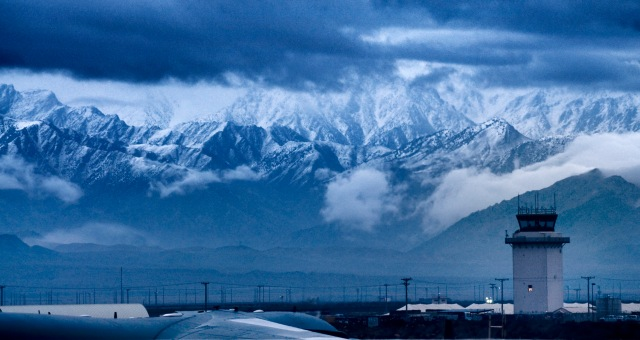 view of mountains from Bagram Air Field, Afghanistan; storm clouds gather and the mountains are dusted with snow