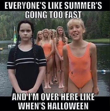 "(Addams Family Values) blond white girls lined up in matching orange suimsuits stand on a dock; Wednesday Addams stands out in her old-fashioned black swimming costume. Text reads, ""Everyone's like summer's going too fast and I'm over here like when's Halloween"""