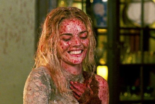 (Ready or Not) Bride in torn, burned, bloody wedding dress, covered in blood spatter, hair matted with blood and grit, giggles.
